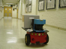 Experimental environment and the Pioneer 3-DX robot with a SICK LMS-200 laser ranger. The boxes were placed to create corner features for prediction.